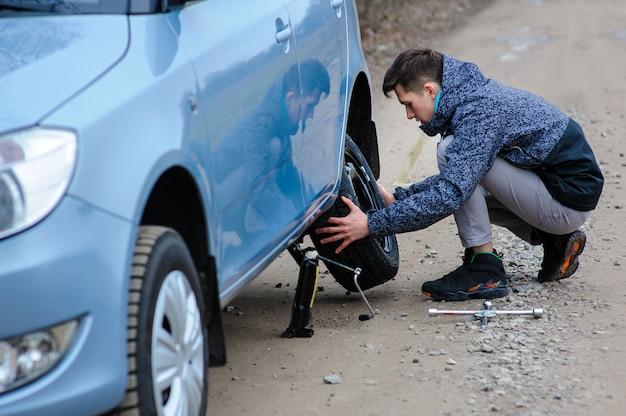 Un homme a cassé une roue d'une voiture et la change toute seule sur la route.