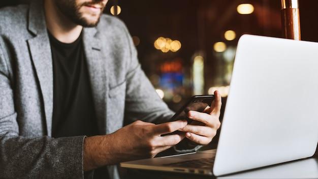 Homme casual à l'aide de téléphone portable dans un café