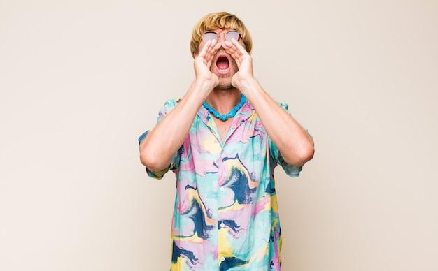 Homme de caucase adulte blond se sentant heureux, excité et positif, donnant un grand cri avec les mains à côté de la bouche, appelant