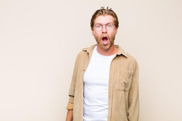 Homme de caucase adulte blond se sentant terrifié et choqué, avec la bouche grande ouverte de surprise