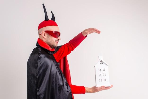 Homme caucasien adulte en costume d'halloween avec bâtiment décoratif dans ses mains isolé sur blanc.