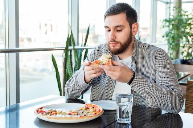 Homme caucasien affamé mangeant la pizza italienne dans la pizzeria. délicieuse pizza au café.