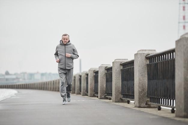 Homme caucasien âgé déterminé en costume de sport gris balançant les bras tout en courant seul par une matinée froide
