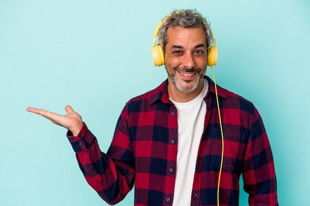 Homme caucasien d'âge moyen écoutant de la musique isolée sur fond bleu montrant un espace de copie sur une paume et tenant une autre main sur la taille.