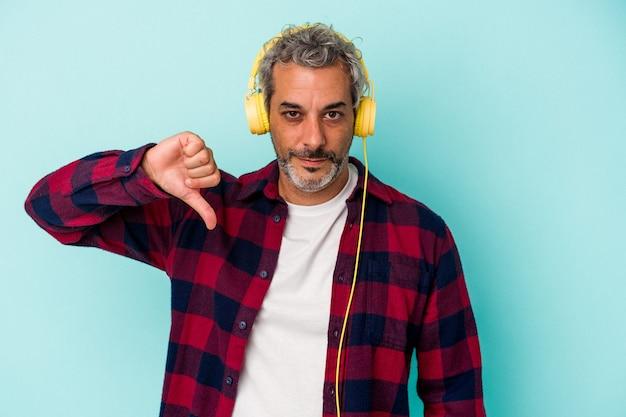 Homme caucasien d'âge moyen écoutant de la musique isolée sur fond bleu montrant un geste d'aversion, les pouces vers le bas. notion de désaccord.