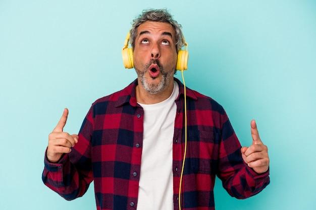 Homme caucasien d'âge moyen écoutant de la musique isolée sur fond bleu pointant vers le haut avec la bouche ouverte.