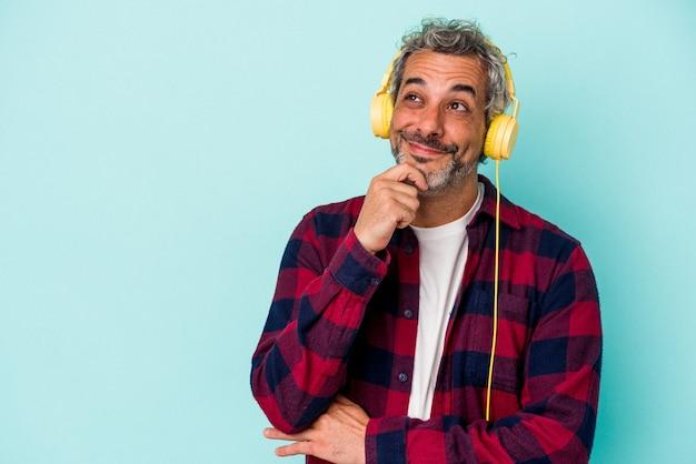 Homme caucasien d'âge moyen écoutant de la musique isolée sur fond bleu regardant de côté avec une expression douteuse et sceptique.