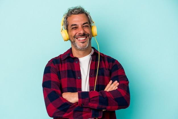 Homme caucasien d'âge moyen écoutant de la musique isolée sur fond bleu en riant et en s'amusant.