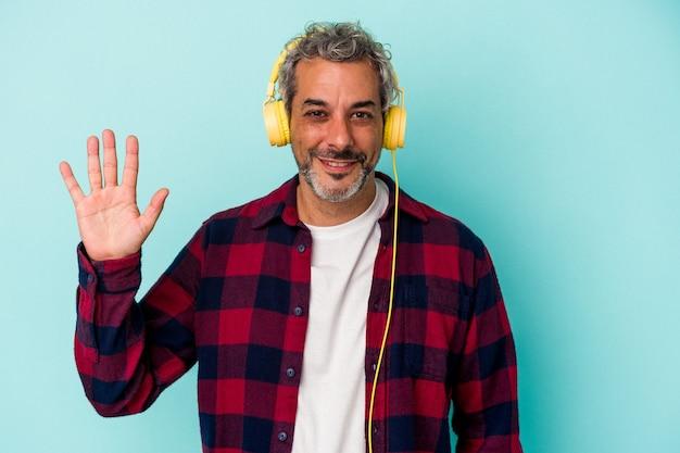 Homme caucasien d'âge moyen écoutant de la musique isolée sur fond bleu souriant joyeux montrant le numéro cinq avec les doigts.