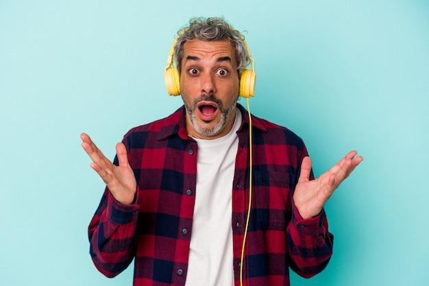 Homme caucasien d'âge moyen écoutant de la musique isolée sur fond bleu surpris et choqué.