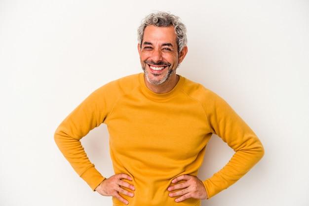 Homme caucasien d'âge moyen isolé sur fond blanc confiant en gardant les mains sur les hanches.