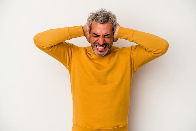 Homme caucasien d'âge moyen isolé sur fond blanc couvrant les oreilles avec les mains essayant de ne pas entendre un son trop fort.