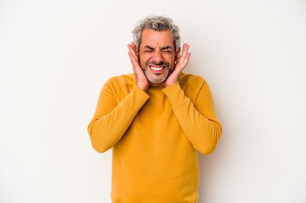 Homme caucasien d'âge moyen isolé sur fond blanc couvrant les oreilles avec les mains.