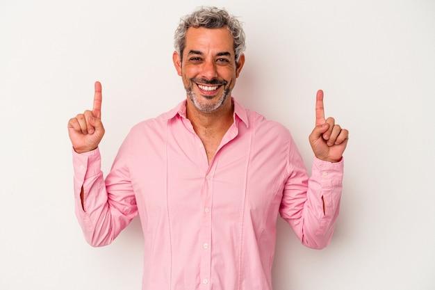 Homme caucasien d'âge moyen isolé sur fond blanc indique avec les deux doigts antérieurs montrant un espace vide.