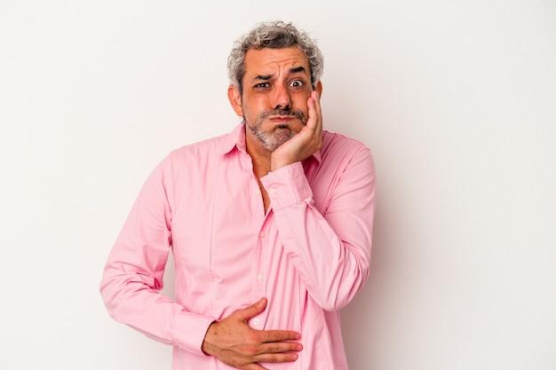 L'homme caucasien d'âge moyen isolé sur fond blanc souffle les joues, a une expression fatiguée. concept d'expression faciale.