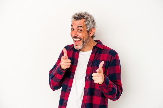 Homme caucasien d'âge moyen isolé sur fond blanc sourires joyeux pointant vers l'avant.