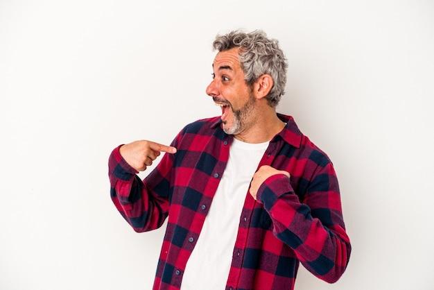 Homme caucasien d'âge moyen isolé sur fond blanc surpris en pointant avec le doigt, souriant largement.