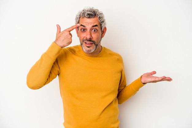 Homme caucasien d'âge moyen isolé sur fond blanc tenant et montrant un produit à portée de main.