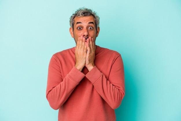 Homme caucasien d'âge moyen isolé sur fond bleu choqué couvrant la bouche avec les mains.