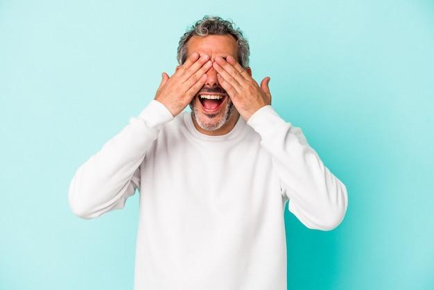 Un homme caucasien d'âge moyen isolé sur fond bleu couvre les yeux avec les mains, sourit largement en attendant une surprise.