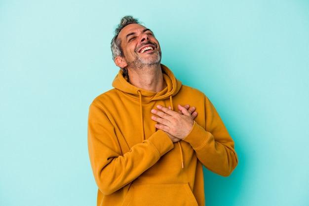 Homme caucasien d'âge moyen isolé sur fond bleu en riant en gardant les mains sur le cœur, concept de bonheur.