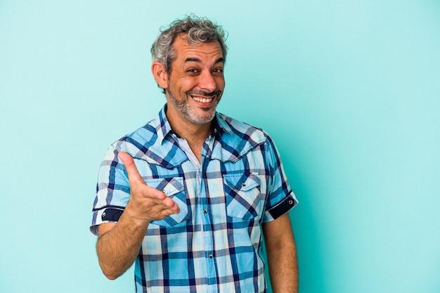 Homme caucasien d'âge moyen isolé sur fond bleu s'étendant la main à la caméra en geste de salutation.
