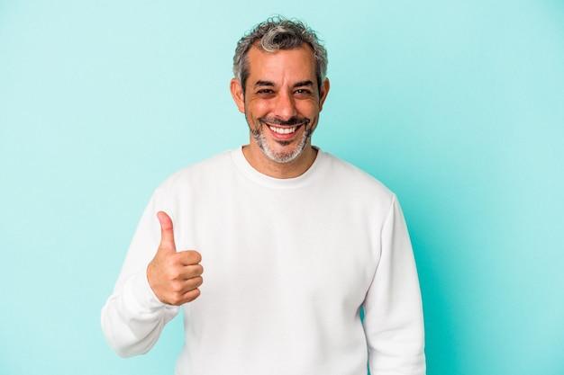 Homme caucasien d'âge moyen isolé sur fond bleu souriant et levant le pouce vers le haut