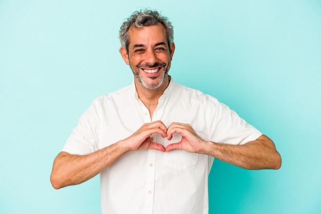 Homme caucasien d'âge moyen isolé sur fond bleu souriant et montrant une forme de coeur avec les mains.