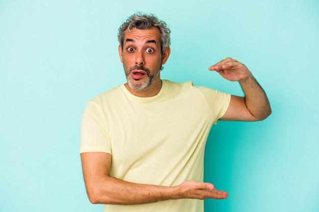 Homme caucasien d'âge moyen isolé sur fond bleu tenant quelque chose avec les deux mains, présentation du produit.
