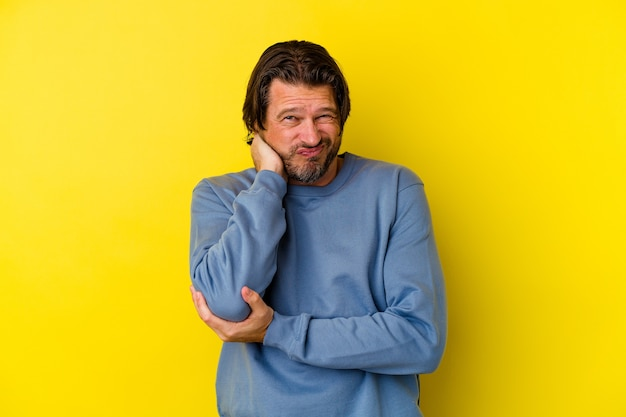 Homme caucasien d'âge moyen isolé sur fond jaune, massage du coude, souffrant après un mauvais mouvement.