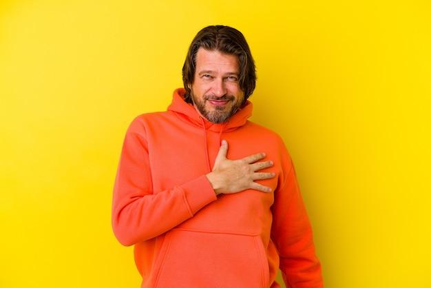Homme caucasien d'âge moyen isolé sur fond jaune, prêtant serment, mettant la main sur la poitrine.
