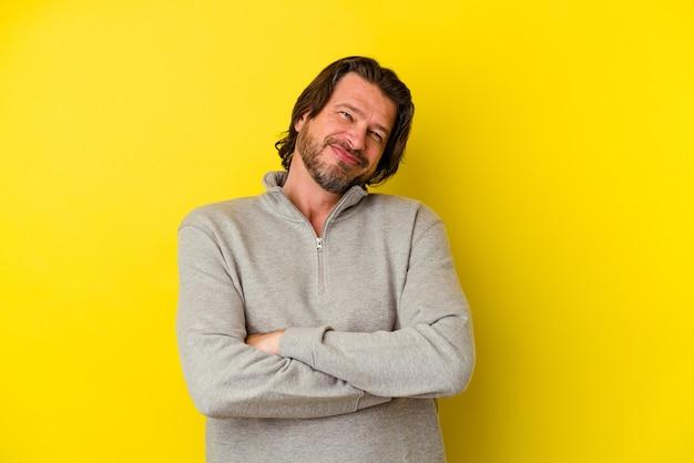 Homme caucasien d'âge moyen isolé sur fond jaune qui se sent confiant, croisant les bras avec détermination.