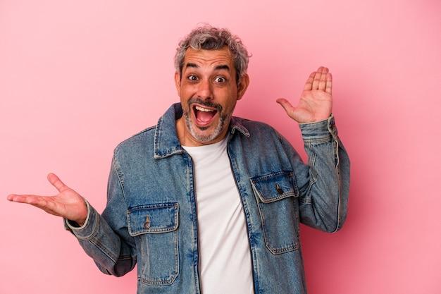 Un homme caucasien d'âge moyen isolé sur fond rose détient un espace de copie sur une paume, garde la main sur la joue. émerveillé et ravi.