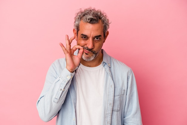 Homme caucasien d'âge moyen isolé sur fond rose avec les doigts sur les lèvres gardant un secret.