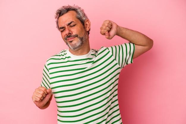 Homme caucasien d'âge moyen isolé sur fond rose étirant les bras, position détendue.