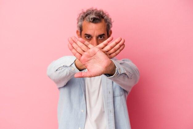 Homme caucasien d'âge moyen isolé sur fond rose faisant un geste de déni