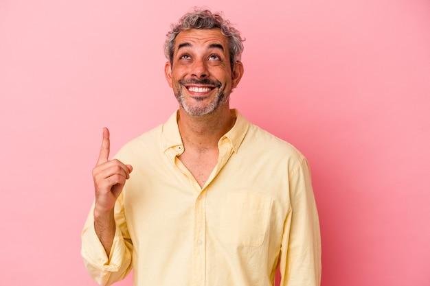 Homme caucasien d'âge moyen isolé sur fond rose indique avec les deux doigts antérieurs montrant un espace vide.