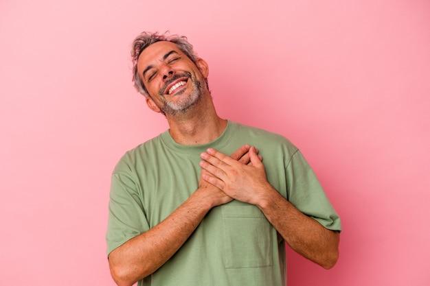Homme caucasien d'âge moyen isolé sur fond rose en riant en gardant les mains sur le cœur, concept de bonheur.