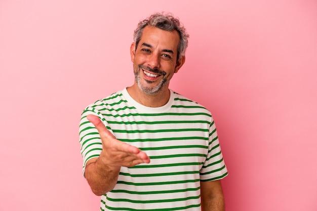 Homme caucasien d'âge moyen isolé sur fond rose s'étendant la main à la caméra en geste de salutation.