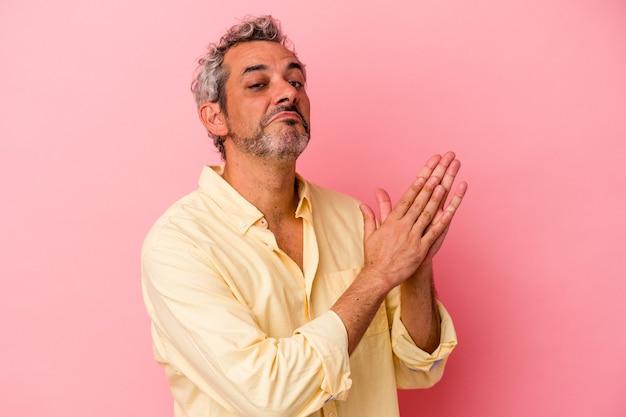 Homme caucasien d'âge moyen isolé sur fond rose se sentant énergique et confortable, se frottant les mains confiant.