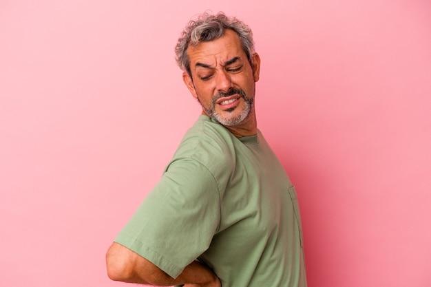 Homme caucasien d'âge moyen isolé sur fond rose souffrant d'un mal de dos.