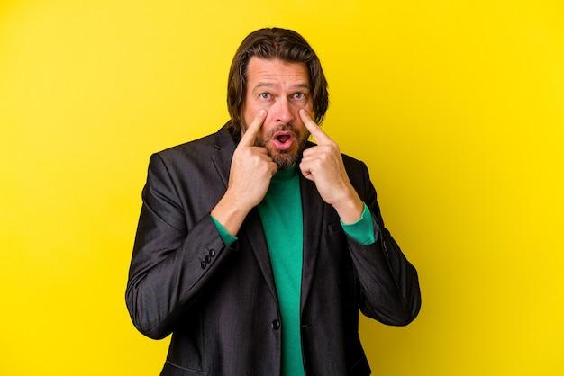 Homme caucasien d'âge moyen isolé sur mur jaune pleurer, mécontent de quelque chose