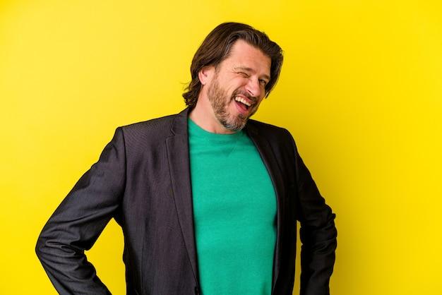 Homme caucasien d'âge moyen isolé sur mur jaune rit et ferme les yeux, se sent détendu et heureux
