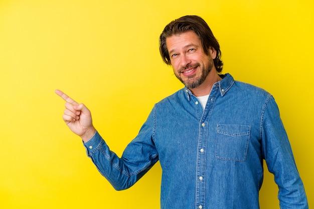 Homme caucasien d'âge moyen isolé sur mur jaune souriant joyeusement pointant avec l'index loin.