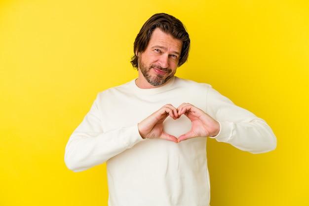 Homme caucasien d'âge moyen isolé sur mur jaune souriant et montrant une forme de coeur avec les mains.