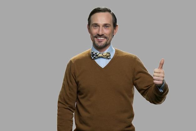 Homme caucasien d'âge moyen montrant le signe du pouce vers le haut. homme souriant regardant la caméra sur fond gris. concept de réussite.