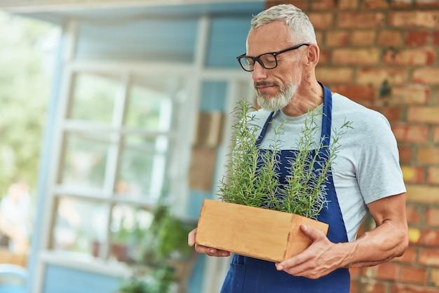 Homme caucasien d'âge moyen reniflant l'arôme de romarin épicé
