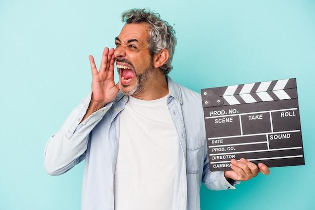 Homme caucasien d'âge moyen tenant un clap isolé sur fond bleu criant et tenant la paume près de la bouche ouverte.