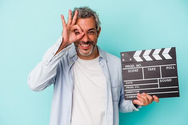 Homme caucasien d'âge moyen tenant un clap isolé sur fond bleu excité en gardant le geste ok sur les yeux.
