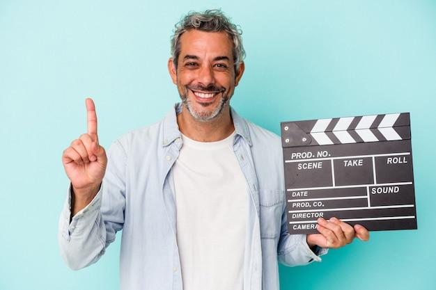 Homme caucasien d'âge moyen tenant un clap isolé sur fond bleu montrant le numéro un avec le doigt.